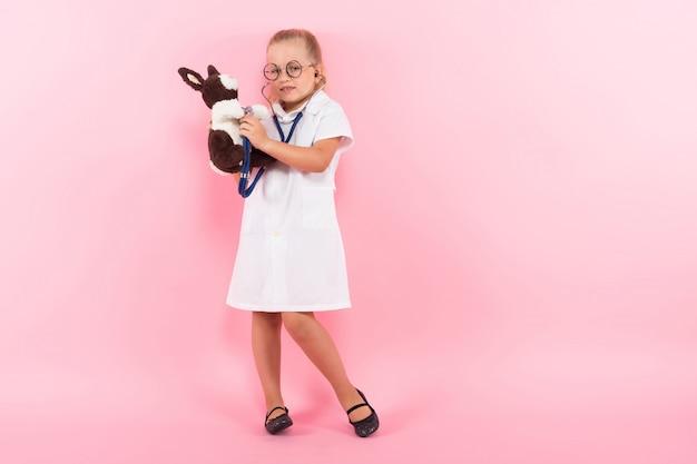 Bambina in costume da medico con il giocattolo