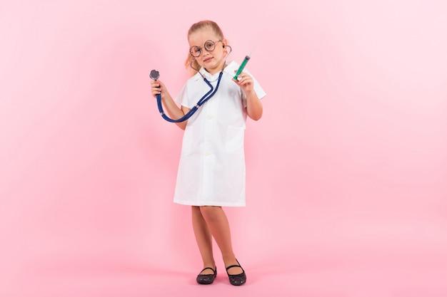 Bambina in costume da medico con iniezione