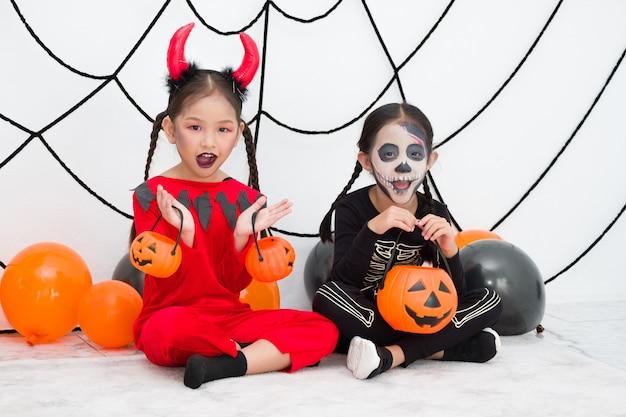 Bambina in costume di carnevale di halloween con jack o lantern (zucca) e palloncino. i bambini asiatici adorabili si prendono in giro allegramente.