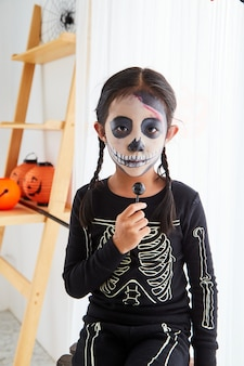 Bambina in costume di halloween a casa