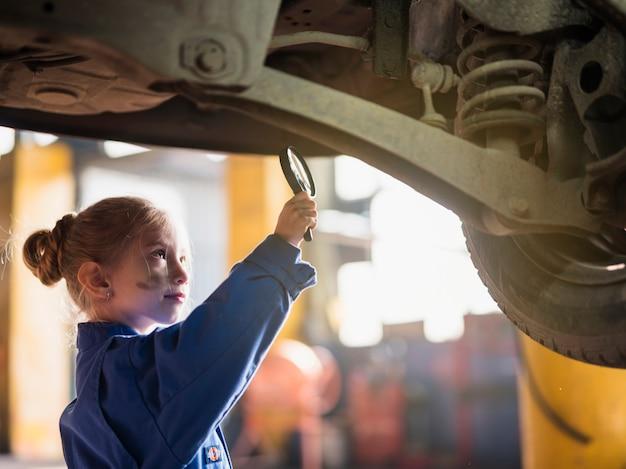 Bambina in generale ispezionando auto con lente d'ingrandimento