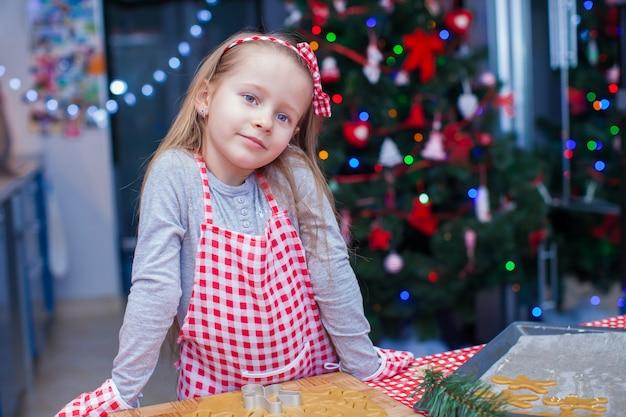 Bambina in guanti che cuociono i biscotti del pan di zenzero di natale
