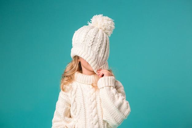Bambina in inverno cappello e maglione lavorato a maglia