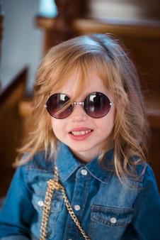 Bambina in jeans camicia e occhiali da sole in posa e sorridente.
