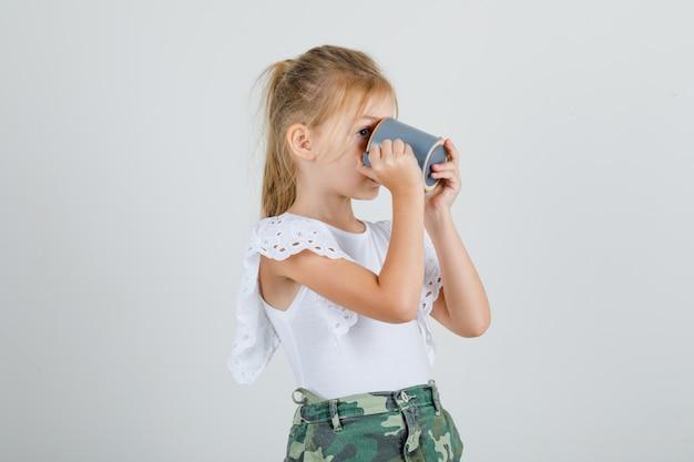 Bambina in maglietta bianca, gonna che beve tazza di tè e sembra assetata