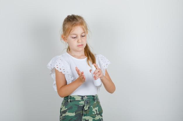 Bambina in maglietta bianca, gonna di pompaggio flacone spray in un'altra mano e guardando attento