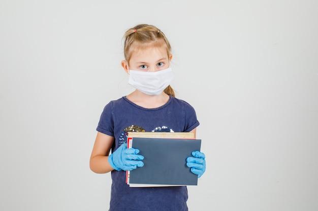 Bambina in maglietta, guanti e libri e taccuini medici della tenuta della maschera e sembrare attenti, vista frontale.