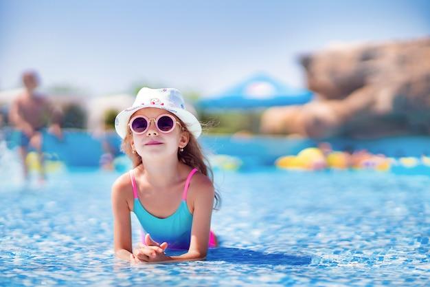 Bambina in occhiali da sole e cappello con unicorno nella piscina all'aperto del resort di lusso in vacanza estiva sull'isola tropicale della spiaggia
