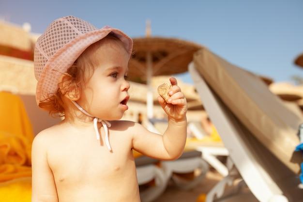 Bambina in panama giocando con un ciottolo sulla spiaggia sotto la protezione degli ombrelloni
