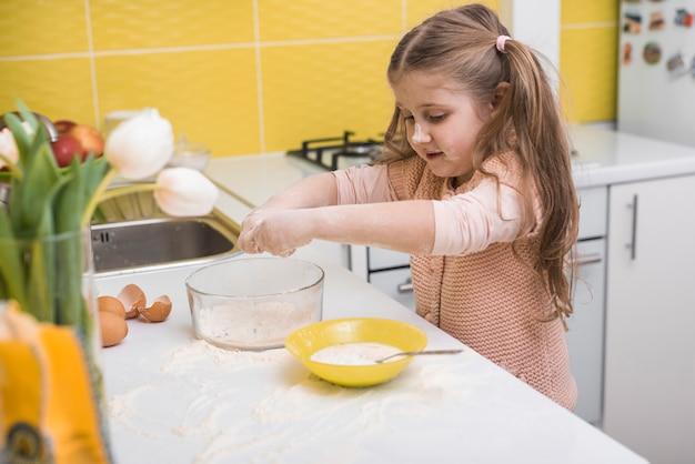 Bambina in piedi al tavolo con ciotola di farina