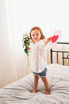 Bambina in piedi con fiori e biglietto di auguri