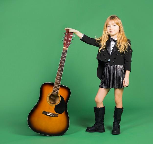 Bambina in piedi con la chitarra acustica