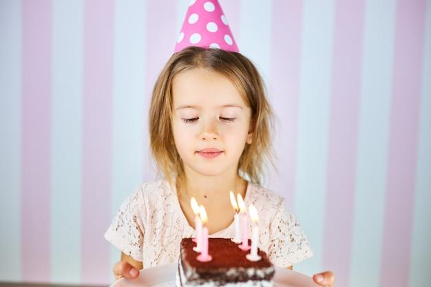 Bambina in protezione di compleanno rosa con torta di compleanno al cioccolato con candele