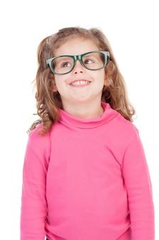 Bambina in rosa con gli occhiali alzando lo sguardo