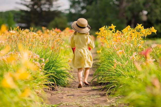 Bambina in stivali di gomma rossi e un cappello di paglia che innaffia i fiori d'innaffiatura rossi nel giardino