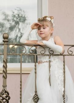 Bambina in un abito da ballo sul balcone