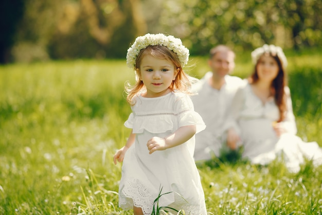 Bambina in un campo in erba con i suoi genitori