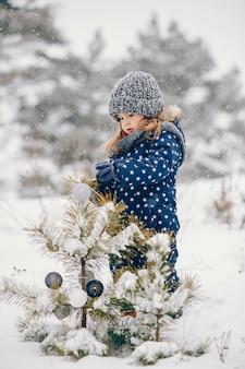 Bambina in un cappello blu che gioca in una foresta di inverno