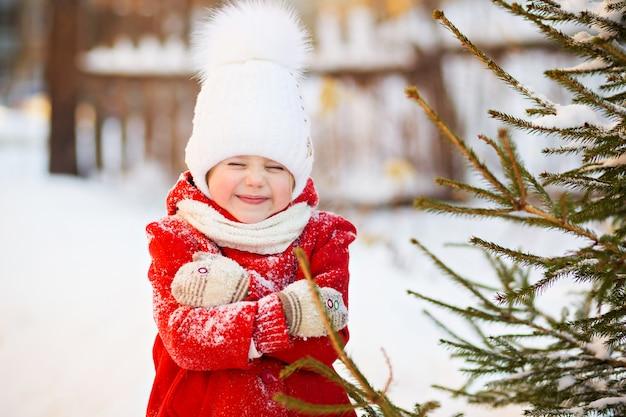 Bambina in un cappotto rosso in inverno, congelata