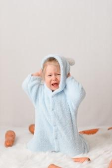 Bambina in un costume da coniglio che mangia le carote.