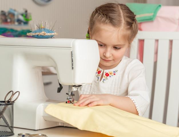 Bambina in un laboratorio di cucito