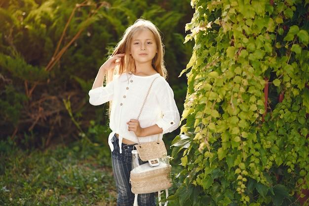 Bambina in un parco che sta con la borsa marrone