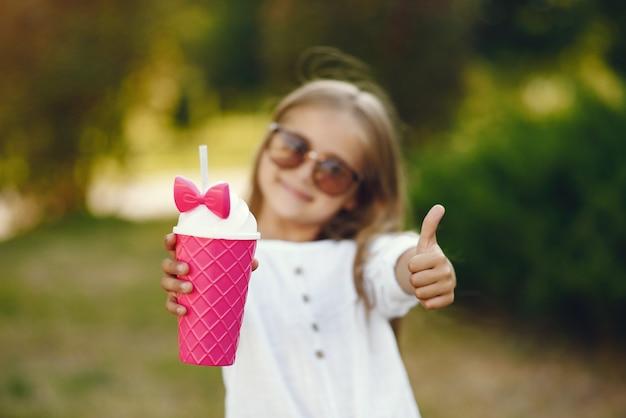 Bambina in un parco che sta con la tazza rosa