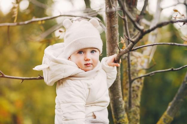 Bambina in un parco in autunno