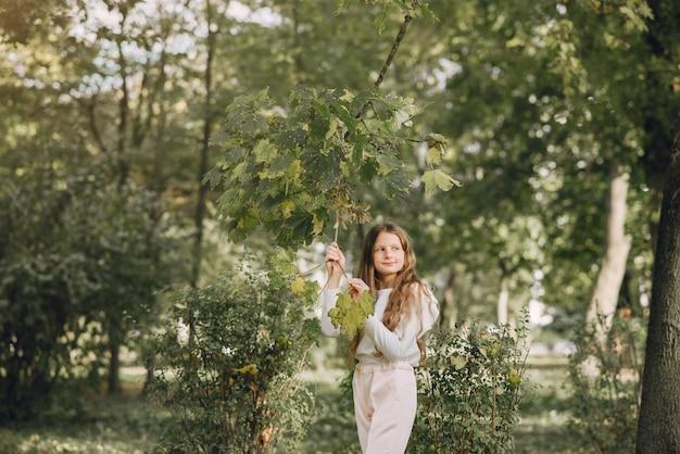 Bambina in un parco in una camicetta bianca