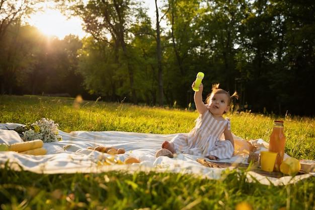 Bambina in un vestito a strisce su un picnic in un parco cittadino