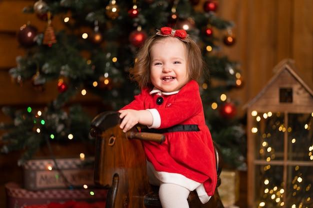Bambina in un vestito rosso festivo su un cavallo a dondolo altalena in legno.