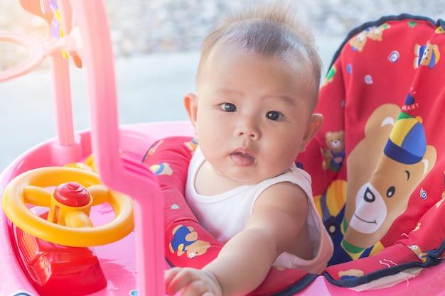 Bambina in una cabina di macchina del giocattolo