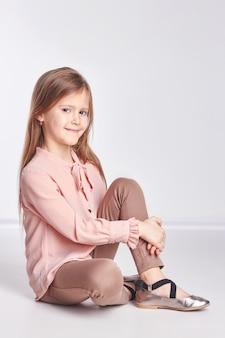 Bambina in una camicia rosa e pantaloni in posa