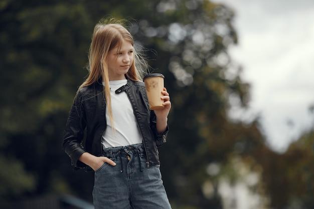Bambina in una maglietta bianca in una città estiva