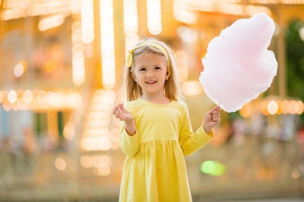 Bambina in una passeggiata in un parco divertimenti a mangiare zucchero filato
