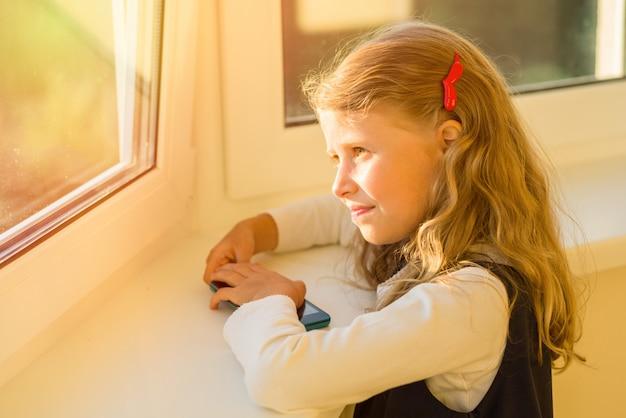 Bambina in uniforme scolastica che guarda fuori dalla finestra