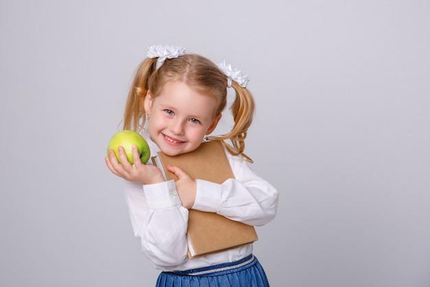 Bambina in uniforme scolastico su fondo bianco che legge un libro