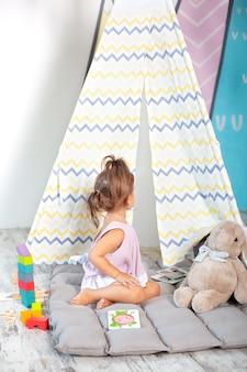 Bambina in wigwam colorato con i giocattoli. bambino gioca con blocchi colorati giocattolo. sviluppo e giocattoli creativi e giochi per bambini piccoli. bambino in una camera da letto con mattoni arcobaleno. il bambino è a casa.
