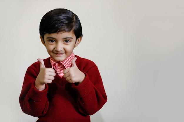 Bambina indiana in uniforme scolastica e mostrando i colpi