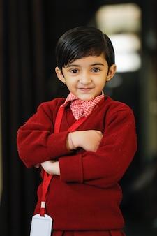 Bambina indiana in uniforme scolastico e che mostra espressione
