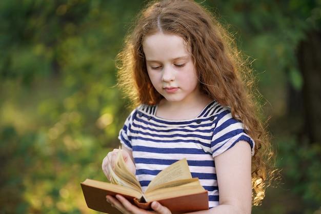Bambina intelligente che legge il libro all'aperto.