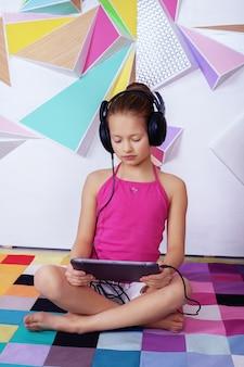 Bambina intelligente con una tavoletta in una stanza di studio.
