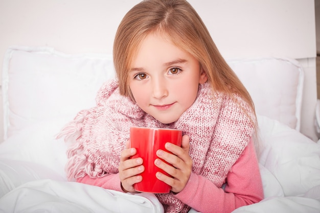 Bambina malata con tè al limone caldo