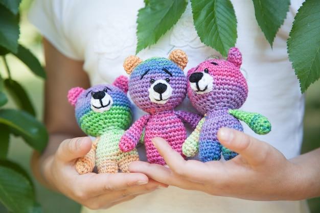 Bambina nel parco che tiene un giocattolo a maglia. fatto a mano, amigurumi