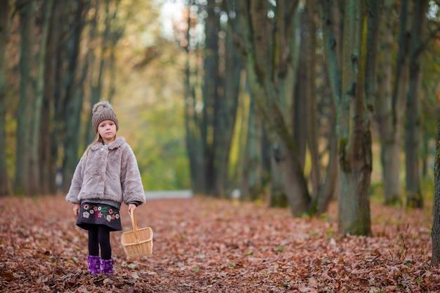 Bambina nel parco di autunno all'aperto