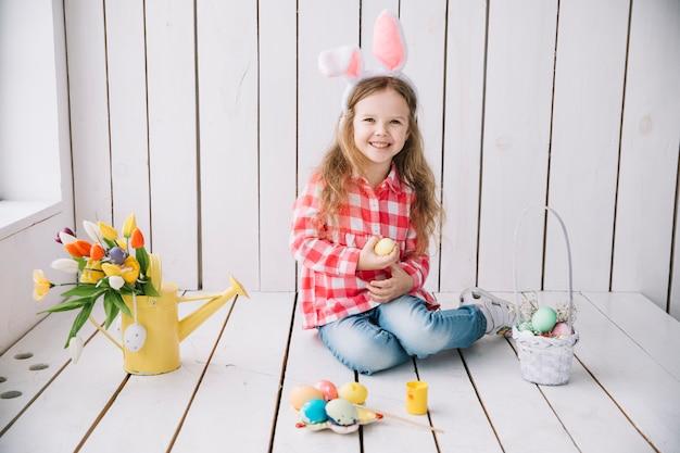 Bambina nelle orecchie del coniglietto che si siede sul pavimento con le uova colorate