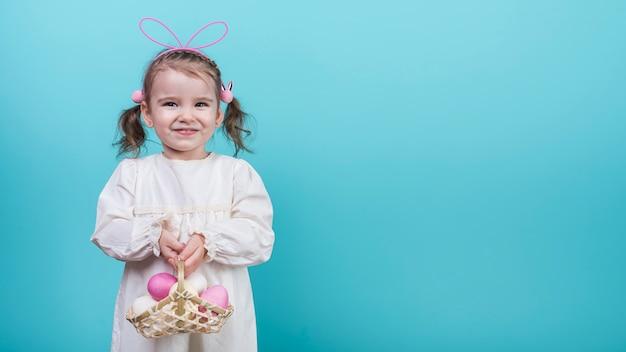 Bambina nelle orecchie del coniglietto che tiene canestro con le uova di pasqua