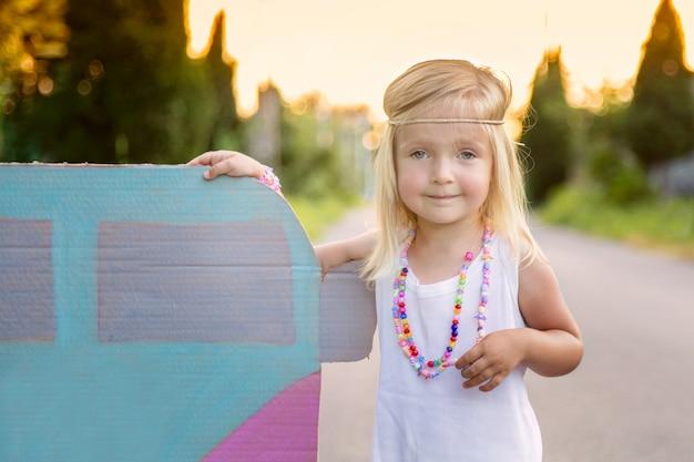 Bambina nello stile di hippy che sta all'aperto sulla strada vicino all'automobile