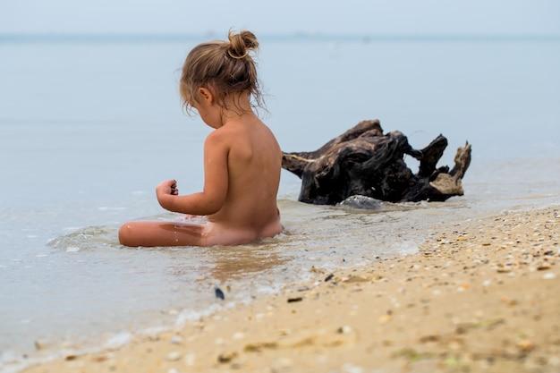 Bambina nuda gioca in mare, bellissima spiaggia