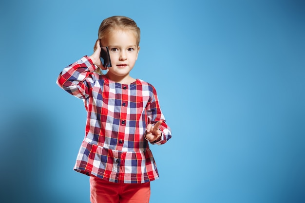 Bambina occupata che parla sul telefono cellulare su fondo blu